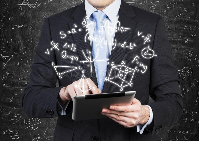 L'homme dans le costume formel tient un comprimé avec la projection de formules de maths sur l'air image libre de droits