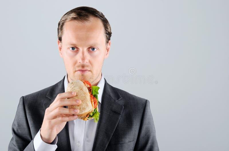 L'homme dans le costume mangeant un délicieux emportent la roulade de viande images libres de droits