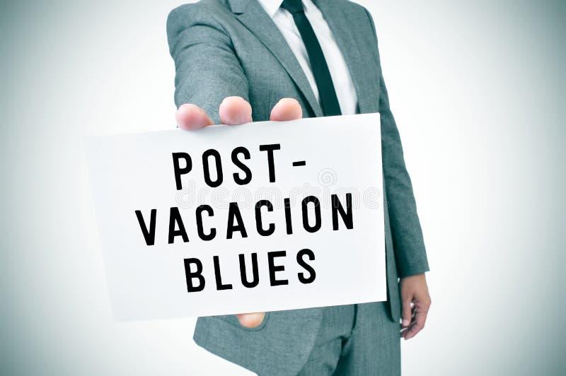 L'homme dans le costume montre une enseigne avec les bleus de courrier-vacances des textes, photo stock