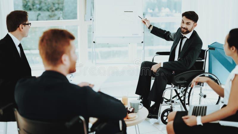 L'homme dans le fauteuil roulant montre l'indicateur au conseil blanc images stock