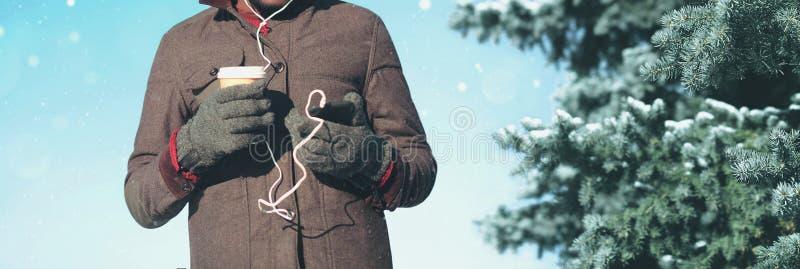 L'homme dans le jour d'hiver avec le smartphone écoute la musique tient la tasse de café photo stock