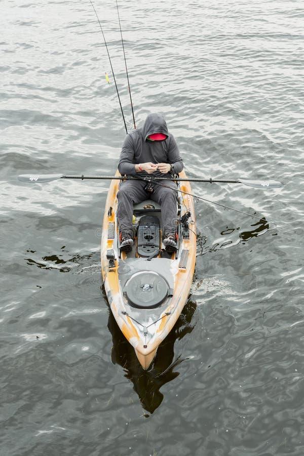 L'homme dans le kayak orange pour pêcher des poissons Il utilise un capot noir image stock