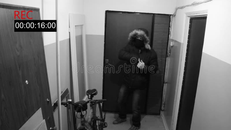 L'homme dans le masque casse la porte dedans et tire le pistolet caché d'appareil-photo photos libres de droits