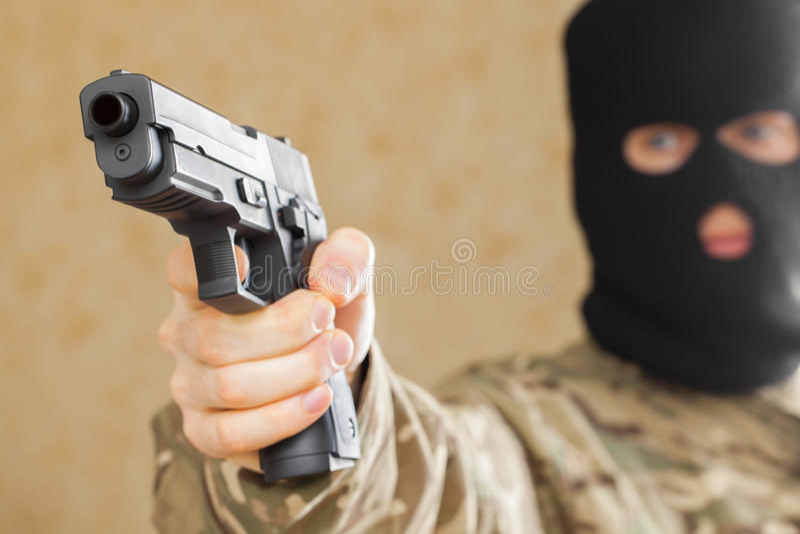 L'homme dans le masque noir tenant l'arme à feu et préparent au tir image libre de droits