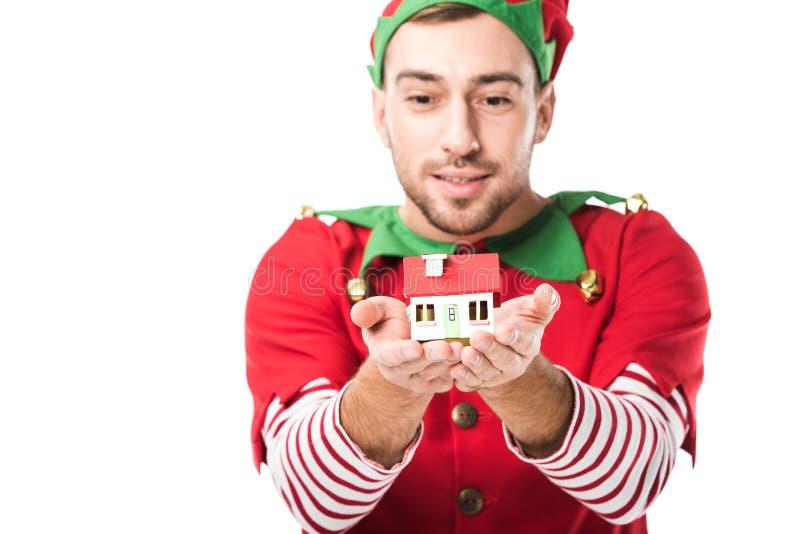 l'homme dans le modèle de maison de participation de costume d'elfe de Noël a isolé images libres de droits