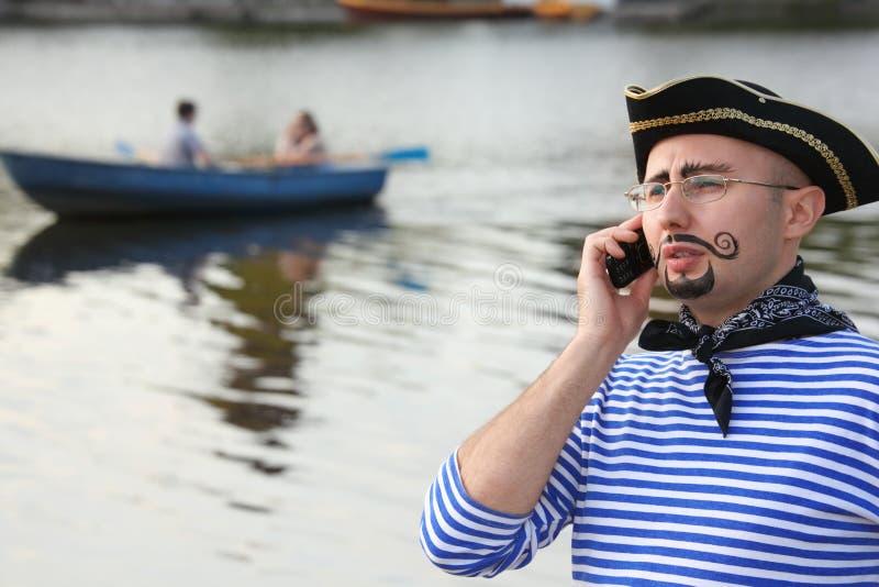 L'homme dans le procès de pirate parle par le téléphone. image libre de droits