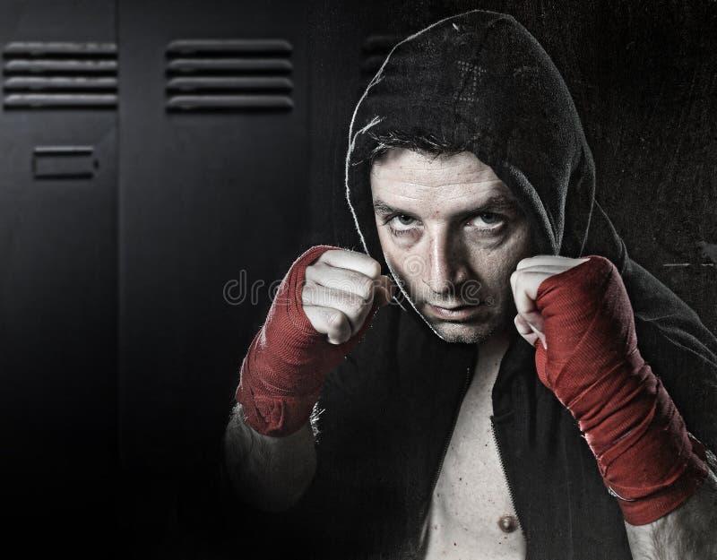 L'homme dans le pullover de hoodie de boxe avec le capot sur la main et le poignet de port principaux a enveloppé prêt pour le co photographie stock libre de droits