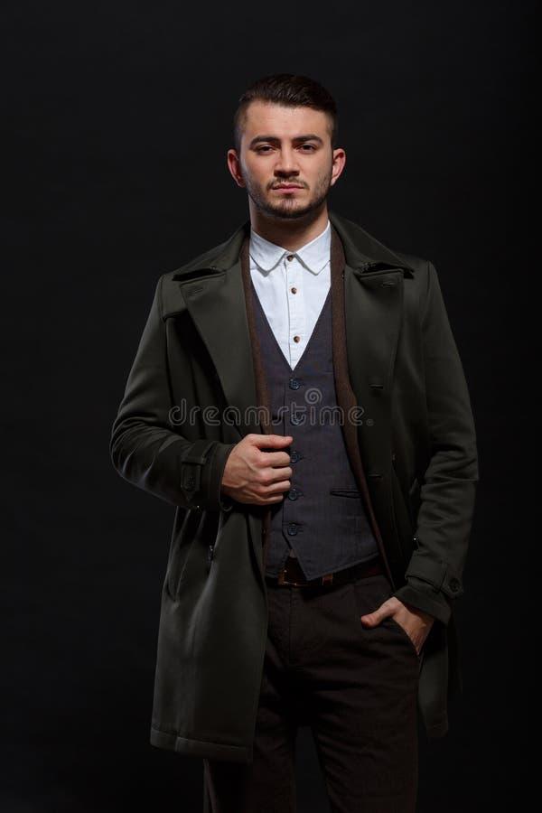 L'homme dans le rétro costume tient une main dans sa poche sur un fond noir photos libres de droits