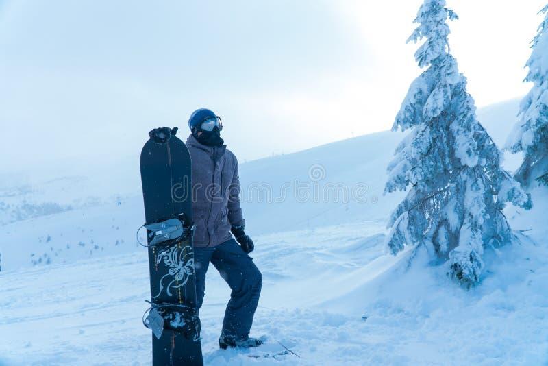 L'homme dans le surf des neiges de neige de montagne Homme tenant un conseil images stock