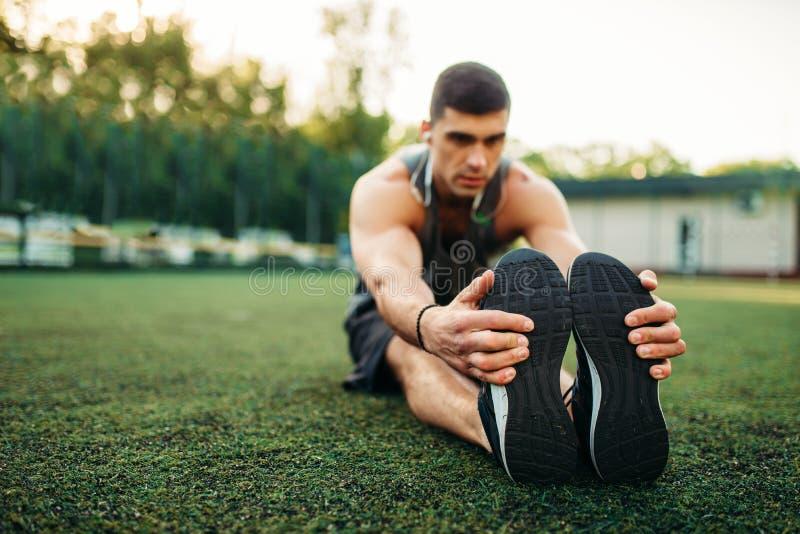 L'homme dans les vêtements de sport réchauffe avant la formation extérieure image libre de droits