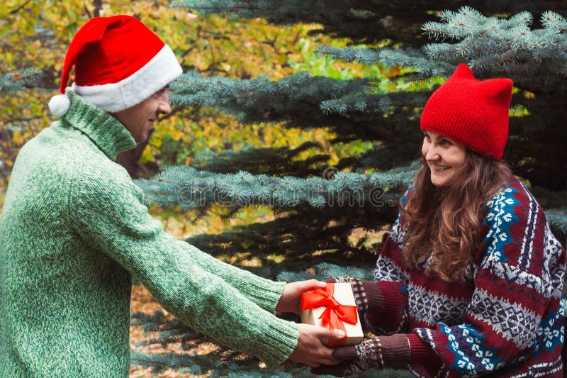 l'homme dans un chapeau Santa Claus de chandail donne un cadeau à une femme images libres de droits