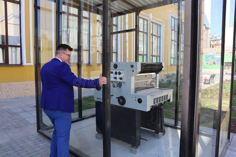 L'homme dans un costume bleu regarde la presse typographique derrière le verre photographie stock libre de droits