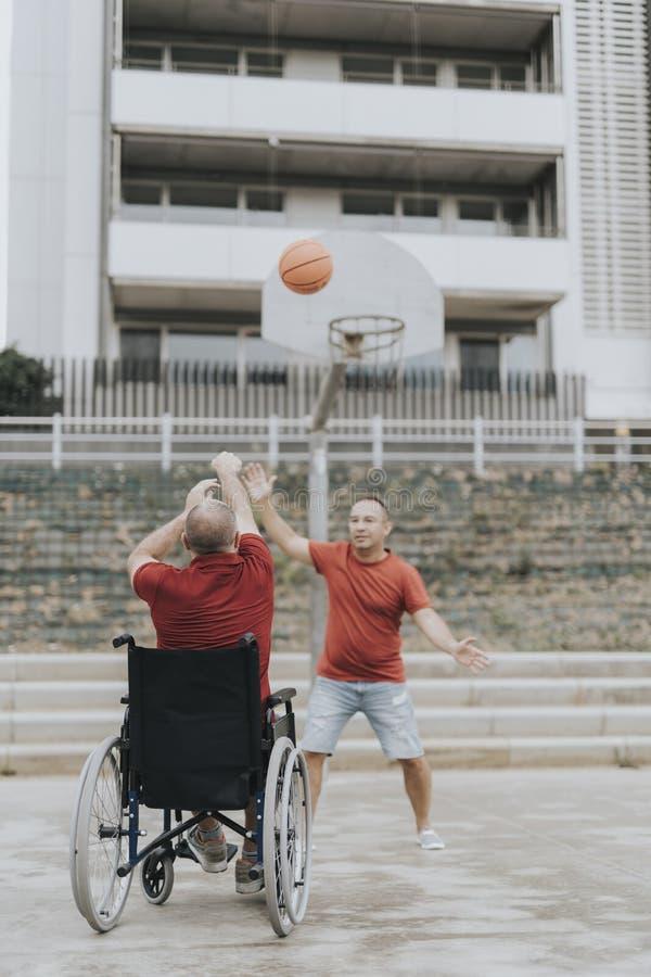 L'homme dans un fauteuil roulant joue au basket-ball avec ses amis en parc de ville photo libre de droits