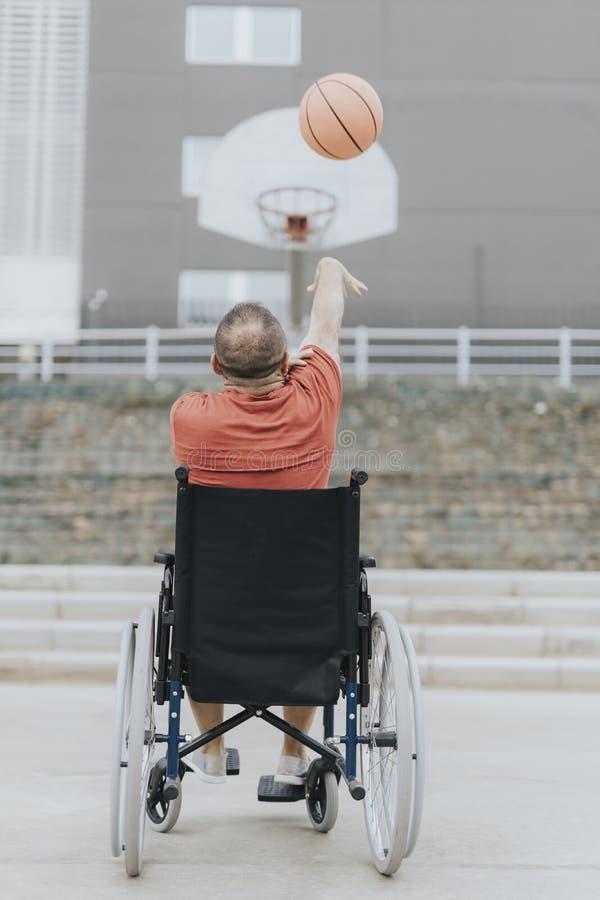 l'homme dans un fauteuil roulant joue seul au basket-ball en parc de ville photos stock