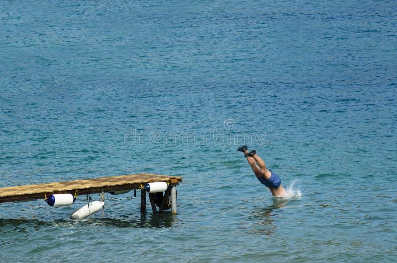 L'homme dans un maillot de bain plonge dans la mer d'un pilier en bois portant les chaussures en caoutchouc noires photo stock