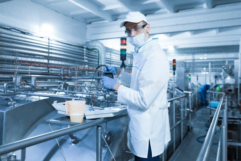 L'homme dans un masque et un peignoir relie le dosimètre à l'installation laitière images libres de droits