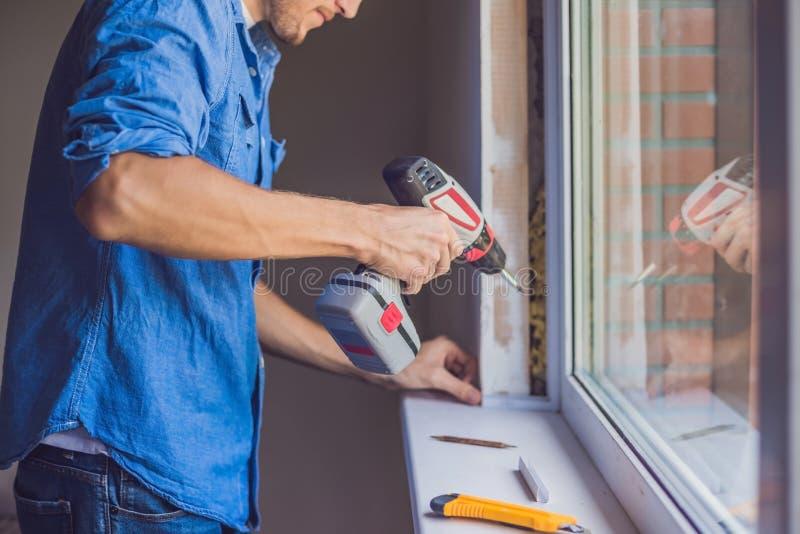 L'homme dans une chemise bleue fait l'installation de fenêtre photo libre de droits