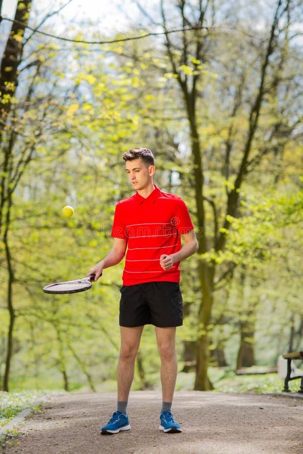 L'homme dans une pose rouge de T-shirt avec une raquette de tennis et une boule sur le fond du parc vert Concept de sport images libres de droits
