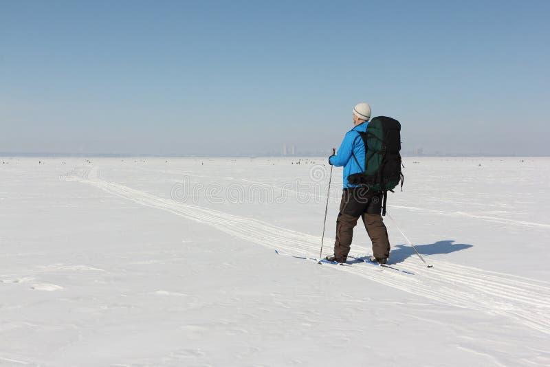 L'homme dans une veste bleue avec un sac à dos skie sur une rivière neigeuse, image stock