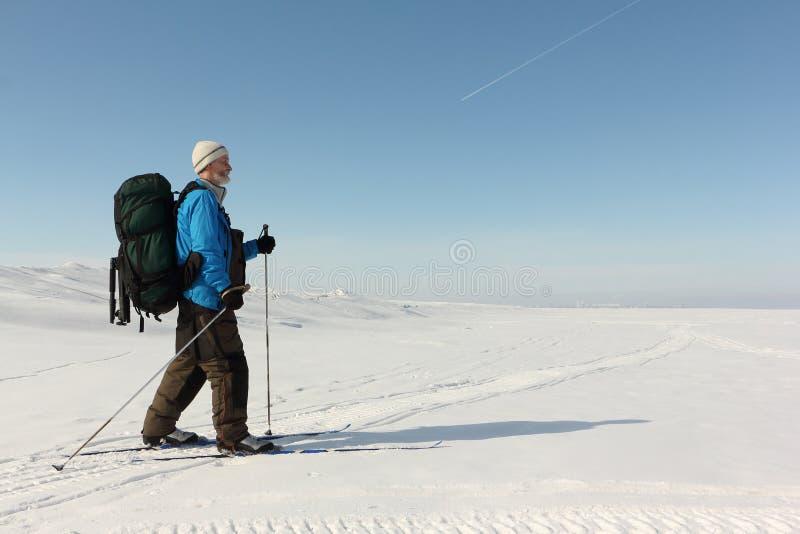 L'homme dans une veste bleue avec un sac à dos skie sur une rivière neigeuse, photos libres de droits