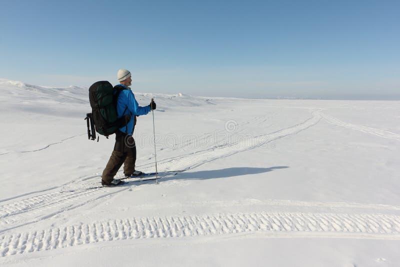 L'homme dans une veste bleue avec un sac à dos skie sur une rivière neigeuse, image libre de droits