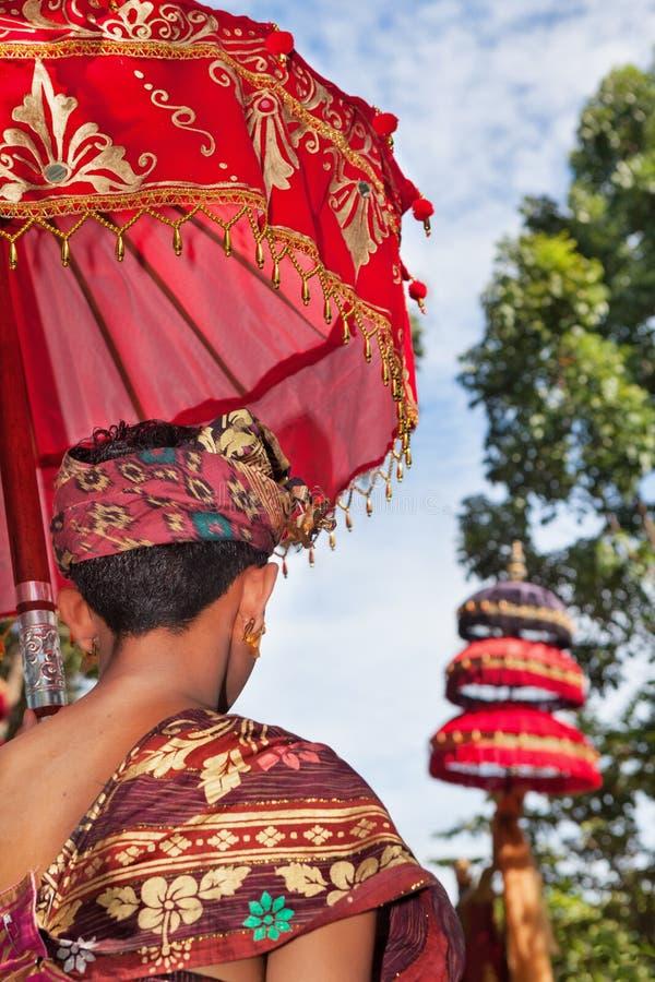 L'homme de Balinese dans des sarongs tiennent le parapluie dans le temple hindou photo stock
