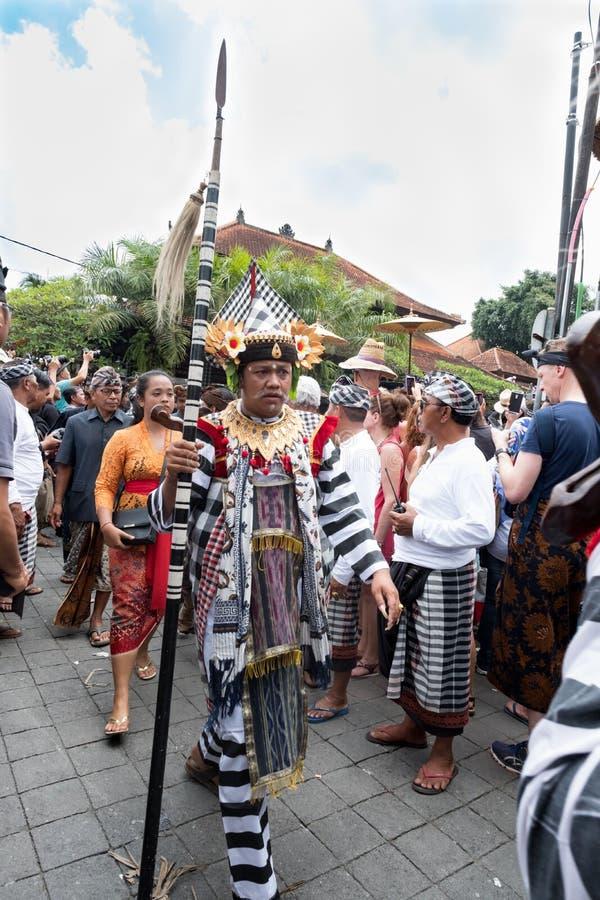 L'homme de Balinese s'est habillé dans les promenades traditionnelles de costume dans le cortège dans Ubud, Bali pendant l'enterr images stock