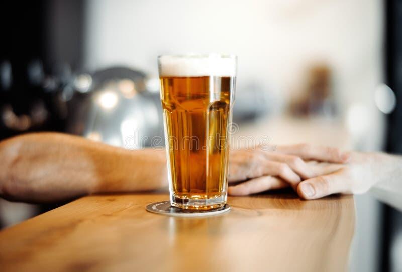 L'homme de barman donne le verre de bière à un client image stock