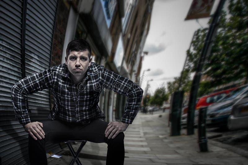 Homme plein d'assurance provocateur s'asseyant à la rue dans prêt à se lever et la pose de combat images libres de droits