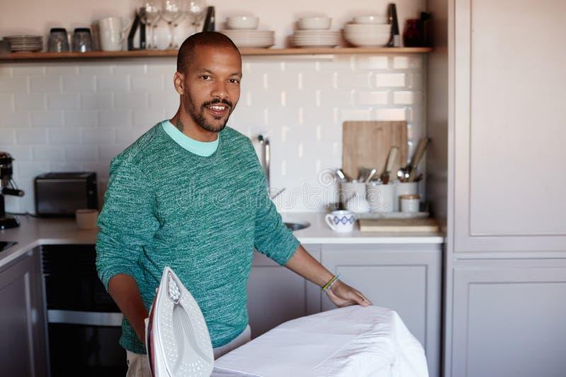 L'homme de couleur américain attirant repasse la chemise blanche à la maison photographie stock