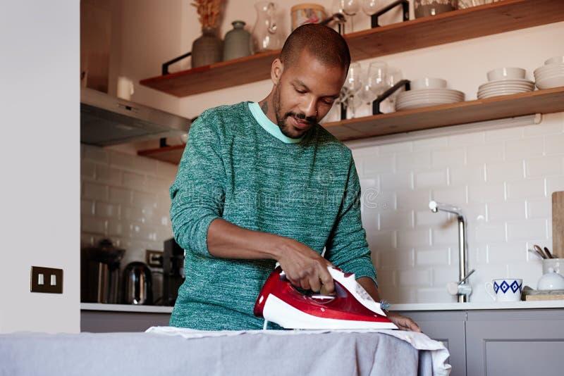 L'homme de couleur américain attirant repasse la chemise blanche à la maison photos stock