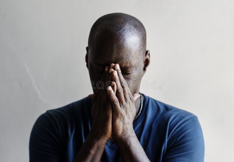 L'homme de couleur avec des mains a couvert son sentiment de visage inquiétées image stock