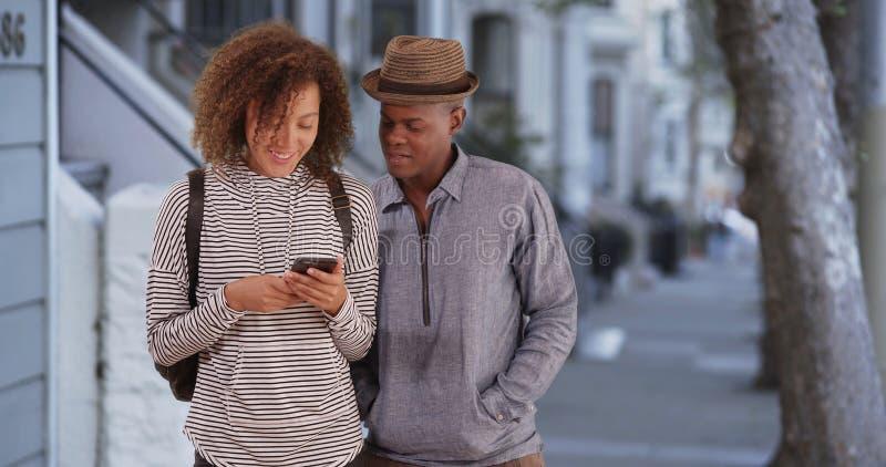L'homme de couleur et la femme se tiennent en dehors de leur appartement de San Francisco réclamant un rideshare photos libres de droits