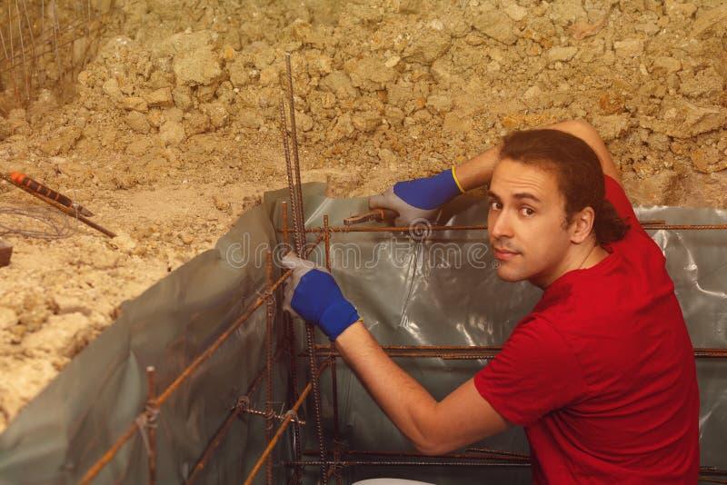 L'homme de DIY tricotent des barres de tige en métal pour le cadre concret photos libres de droits