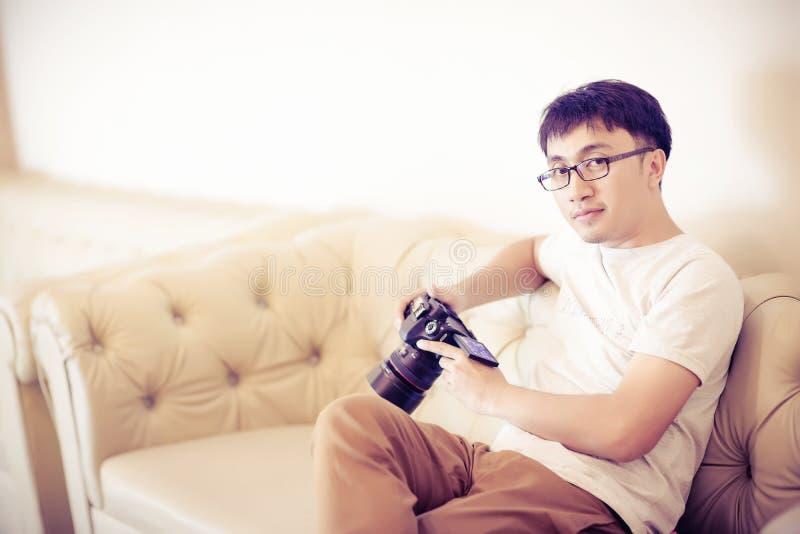 L'homme de fabricant de photographe et de vidéo tiennent l'appareil-photo de DSLR sur sa main sur faire la longueur photographie stock
