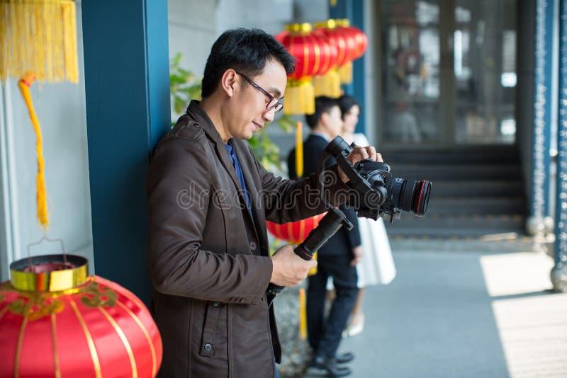 L'homme de fabricant de photographe et de vidéo tiennent l'appareil-photo de DSLR sur sa main sur faire la longueur photographie stock libre de droits