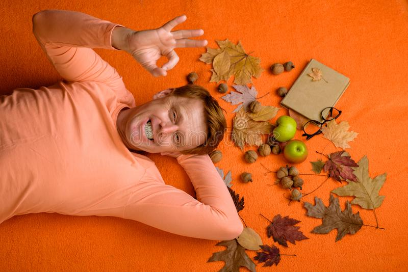 L'homme de gingembre se préparent au jour d'automne Étonnez l'homme roux jouant avec des feuilles et regardant l'appareil-photo L photo libre de droits