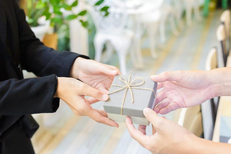 L'homme de mains donne un cadeau aux femmes à l'anniversaire photos stock
