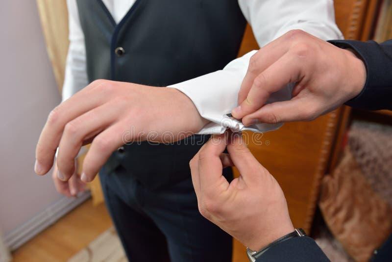 L'homme de mariés aide le marié à mettre dessus les boutons de manchette noirs sur le SL blanc images libres de droits