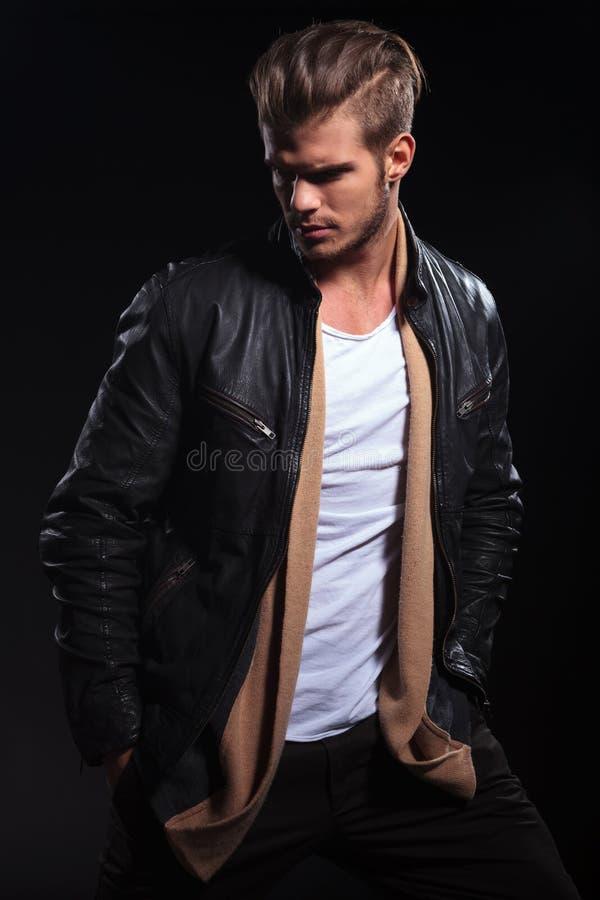 L'homme de mode dans la veste en cuir regarde en arrière au sien photos stock