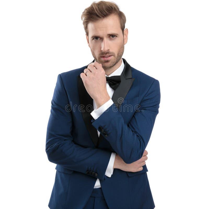 L'homme de mode dans le costume bleu pense avec les bras pliés images stock