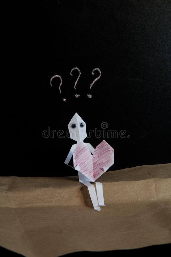 L'homme de papier dans l'amour est déconcerté photo stock