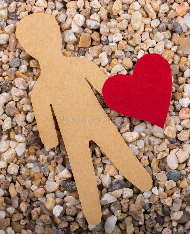 l'homme de papier et une forme de coeur ont coupé du papier photos stock