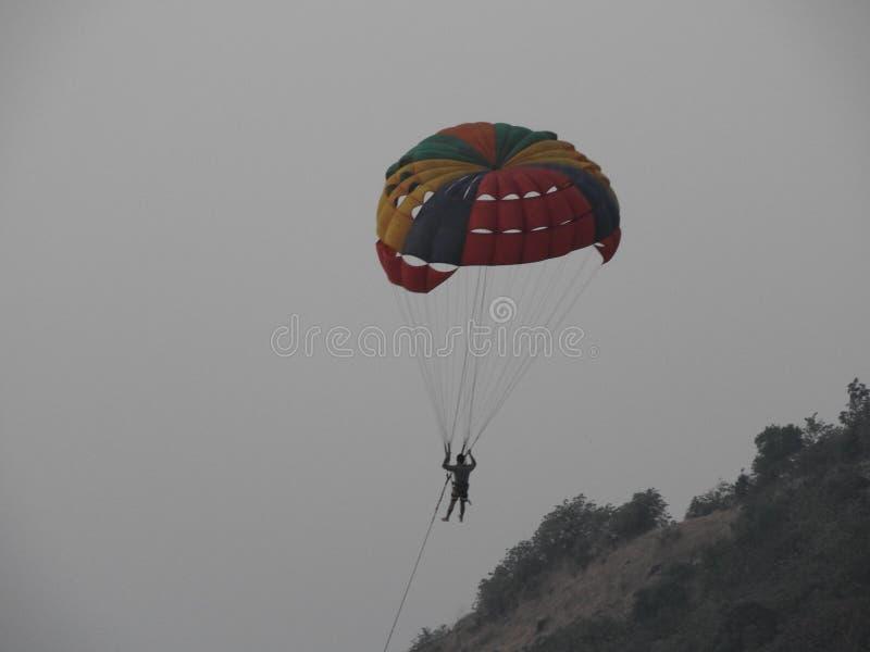 L'homme de parachute contre la colline photos libres de droits