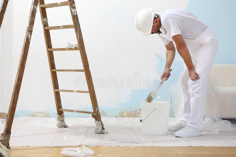 L'homme de peintre au travail prend la couleur avec le pinceau des Bu photo libre de droits