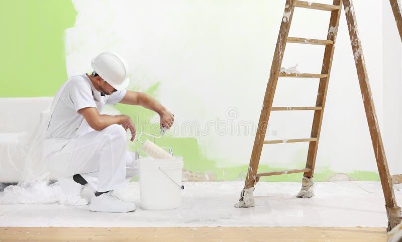 L'homme de peintre au travail prend la couleur avec le pinceau de rouleau de image stock