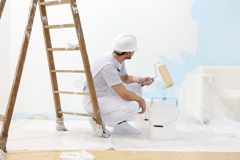 L'homme de peintre au travail prend la couleur avec le rouleau de peinture du b photos stock