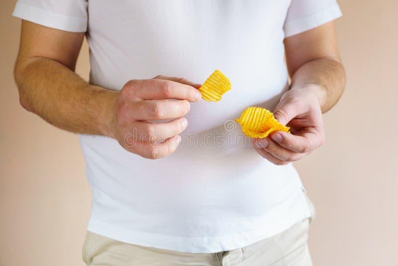 L'homme de poids excessif mange les pommes chips salées d'engraissement images stock