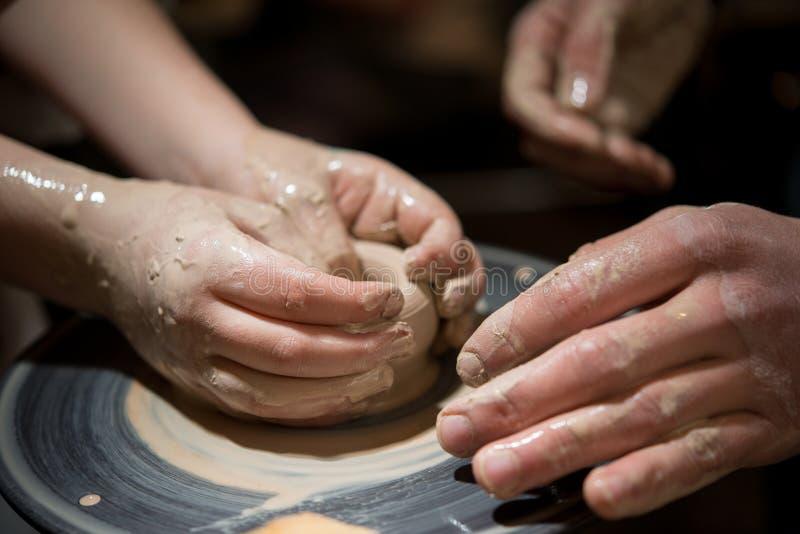 L'homme de professeur enseigne à un enfant comment faire un plat en céramique sur la pile du ` s de potier photos stock