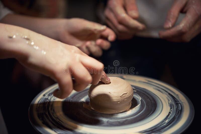 L'homme de professeur enseigne à un enfant comment faire un plat en céramique sur la pile de potiers photographie stock libre de droits